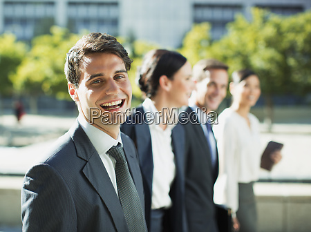 happy businessman walking with colleagues outdoors