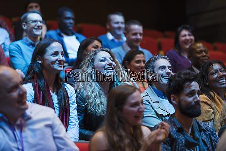 smiling enthusiastic audience in dark auditorium