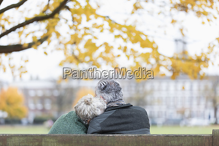 affectionate senior couple cuddling on bench
