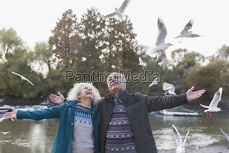 energetic playful senior couple watching flying