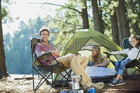 smiling family relaxing at campsite in