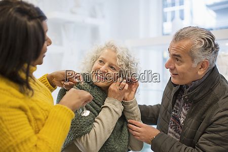 sales assistant helping senior couple jewelry