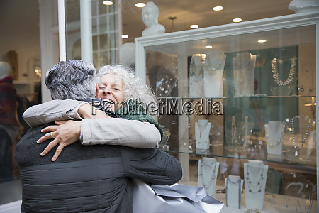 senior couple hugging window shopping at