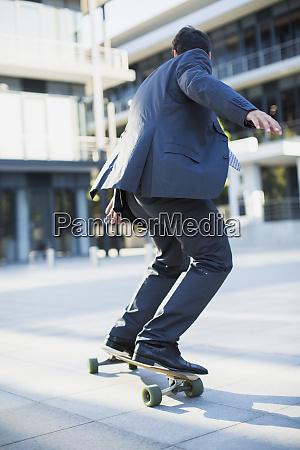 businessman skateboarding on urban sidewalk