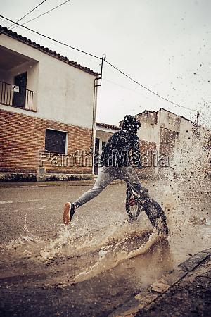 teenage boy splashing water in puddle