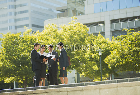 business people discussing paperwork outdoors