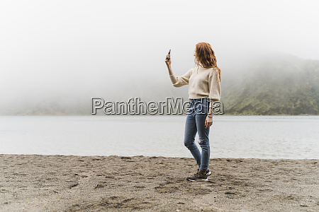 woman photographing at lakeshore while exploring