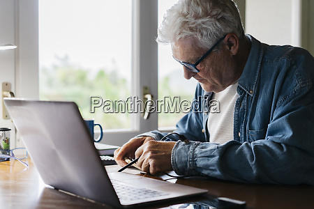 senior man repairing laptop at home
