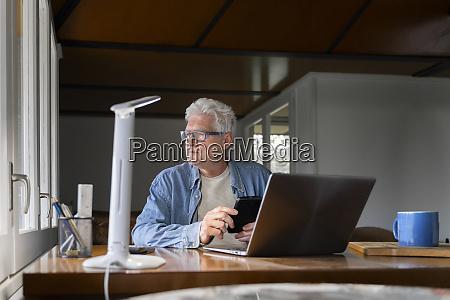 thoughtful senior man holding smart phone