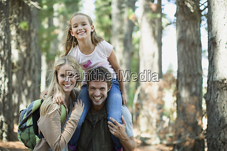smiling family in woods