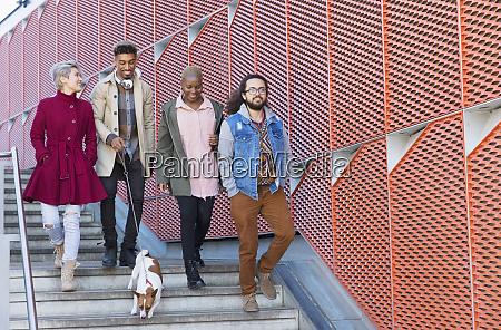 young friends walking down down urban