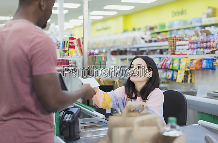 smiling cashier giving receipt to customer