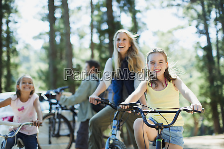 smiling family bike riding in woods