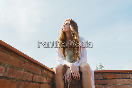 redheaded woman sitting on rooftop and