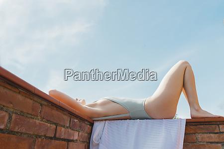 woman wearing swimsuit and enjoying sunlight