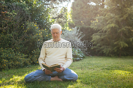 senior man reading a book in