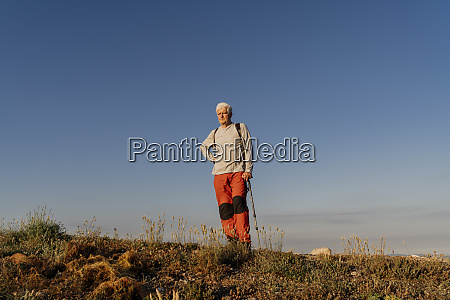 senior man standing with hiking pole