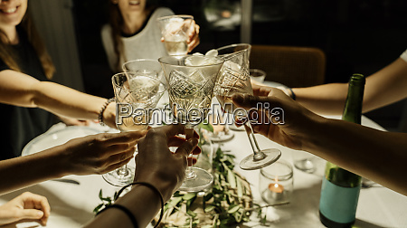 friends making celebratory toast during dinner