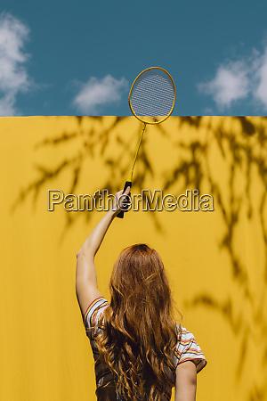 woman holding badminton racket over yellow
