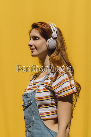 smiling young woman listening music though