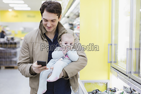 father with baby daughter checking smart