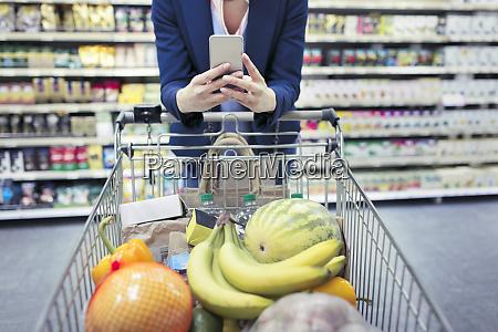 woman with smart phone pushing shopping