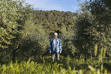 senior man standing between row of