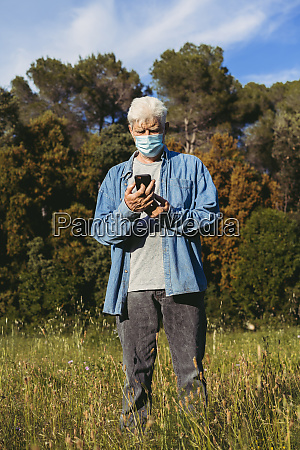 senior man with mask using smartphone