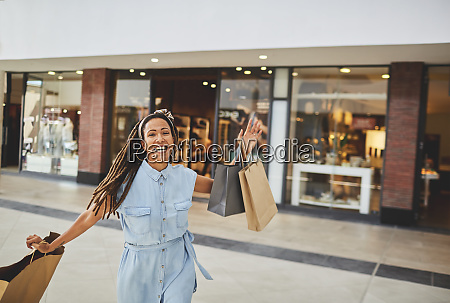 portrait excited woman shopping in mall
