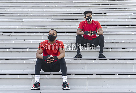 two sportsmen wearing masks sitting on