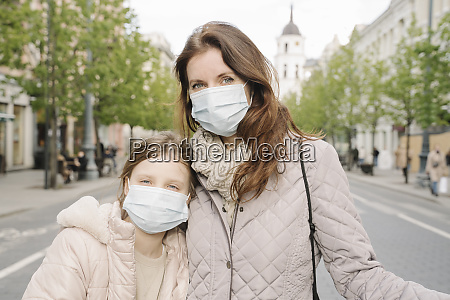 mother and daughter wearing masks standing