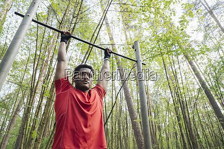 sportsman exercising at high bar in