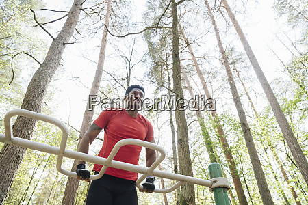 sportsman exercisingat climbing frame in the