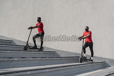 sportsmen wearing face masks with scooters