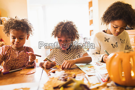 brother and sisters making autumn crafts