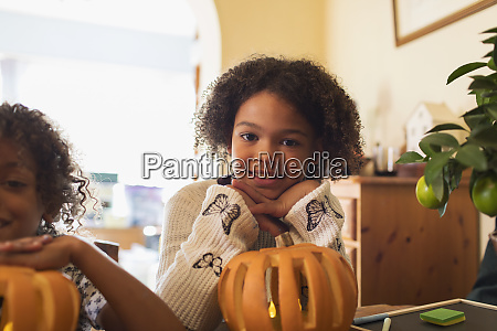 portrait smiling girl carving pumpkin