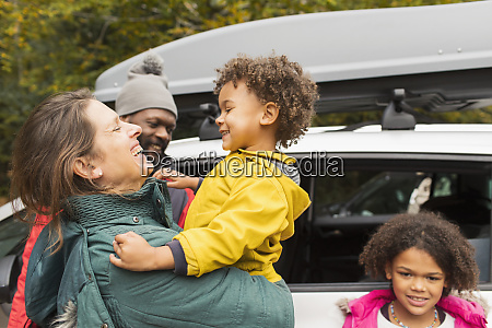 happy family hugging outside car in