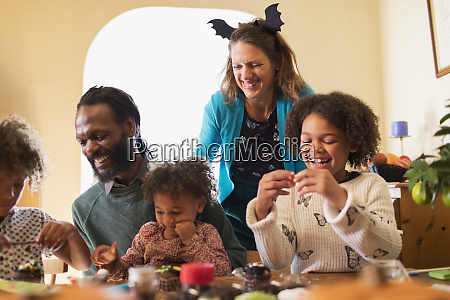 happy family decorating halloween cupcakes at
