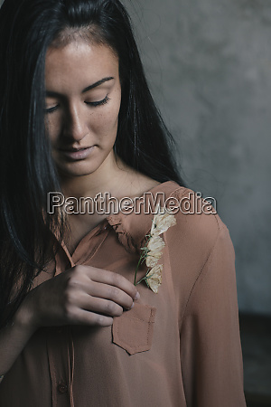 beautiful young woman inserting flowers in