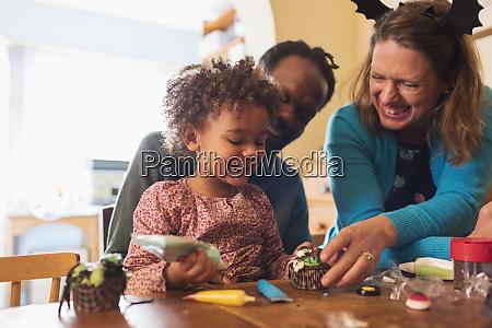 happy family decorating halloween cupcakes