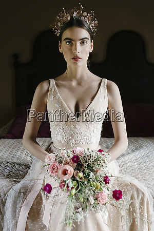young woman wearing wedding dress holding