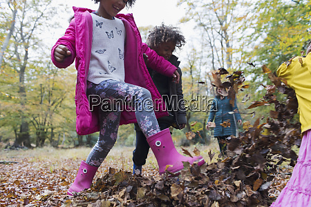 playful kids kicking in autumn leaves