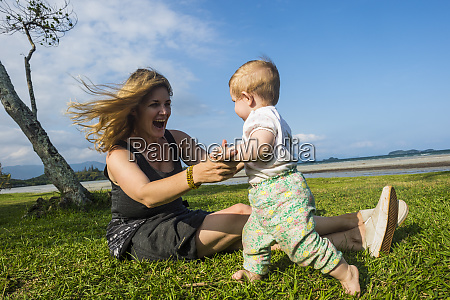 happy mother playing with toddler daughter