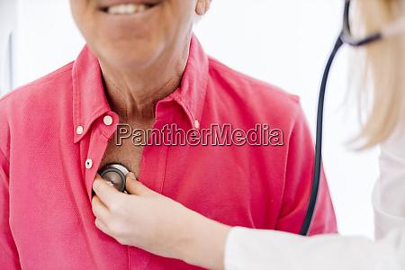 female doctor examining senior patient in