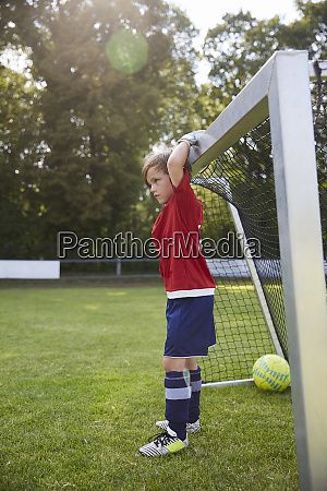 boy in soccer uniform holding goal