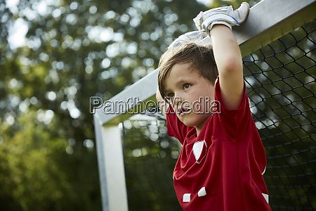 thoughtful soccer boy holding goal post