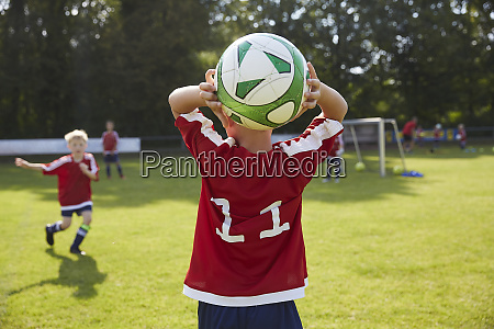 soccer boy throwing ball on field