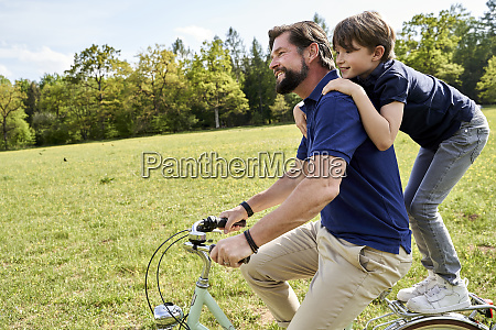 happy father and son enjoying bicycle