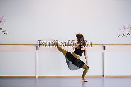 ballerina stretching leg in dance studio