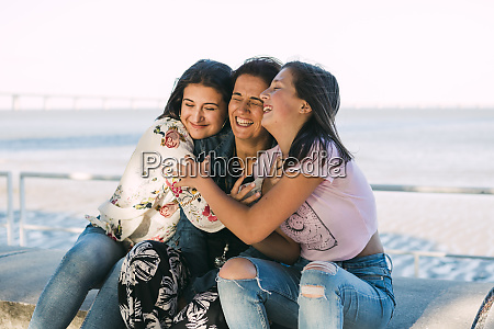 loving daughters embracing cheerful mother while